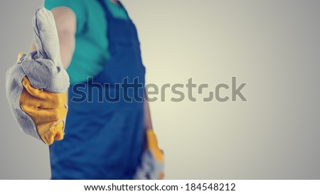 Retro image of workman wearing protective gloves and overalls giving a thumbs up gesture of approval, success and motivation, close up view of the hand with copyspace. - stock photo