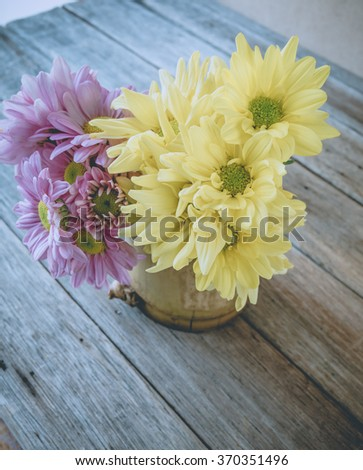 Retro image, pink and yellow flower in bamboo vase on table, vintage background,
