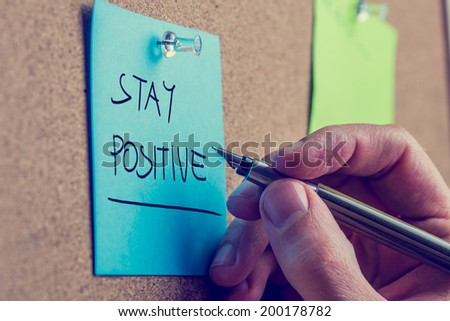 Retro instagram style image of a male hand writing Stay positive on blue post it paper pinned on cork bulletin board.  - stock photo