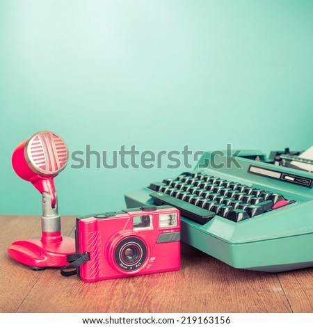 Retro journalism equipments: photo camera, microphone old typewriter on desk front mint green background - stock photo