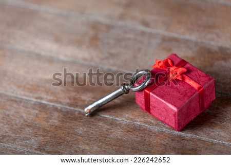 Retro key and little red gift on wooden table. - stock photo