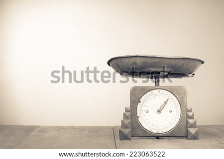 Retro kitchen weight measurement balance on table. Vintage old style sepia photography - stock photo