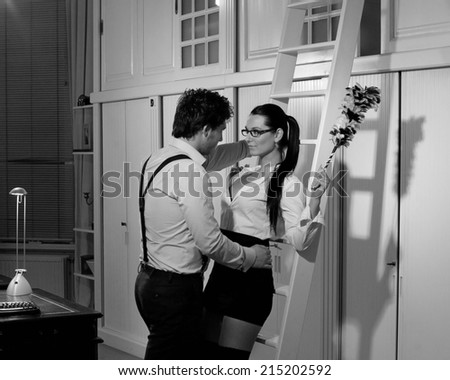 Retro look image with a Beautiful man who is flirting with a sexy woman in his office - stock photo