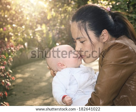 Retro Look Mother Kissing her Sleeping Baby in the Late Afternoon Sunlight - stock photo
