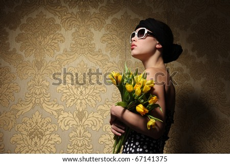 Retro looking young woman in kerchief with yellow flowers looking up against vintage golden wallpaper background. Copyspace.