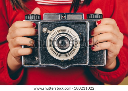 Retro medium format camera in little girl hands with red nails. Some film grain and vintage effect added - stock photo