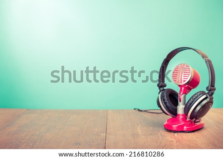 Retro microphone and headphones on table front mint green background - stock photo
