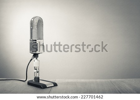 Retro microphone from 50s on table. Vintage old style sepia greyscale photo - stock photo