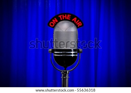 Retro microphone in front of a blue curtain. - stock photo