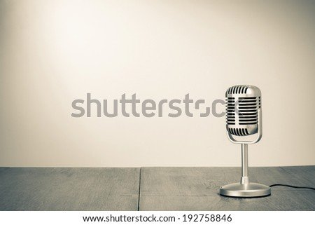 Retro microphone on table sepia photo - stock photo