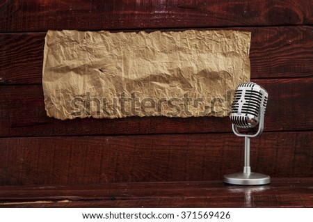 Retro microphone on table with blank paper. Space for text.