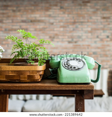 Retro mint green rotary telephone on wood table - stock photo
