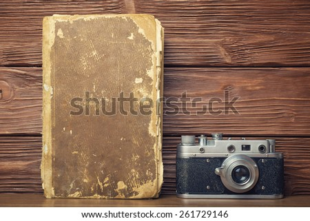 Retro 35mm film camera and old book over rustic wooden background - stock photo