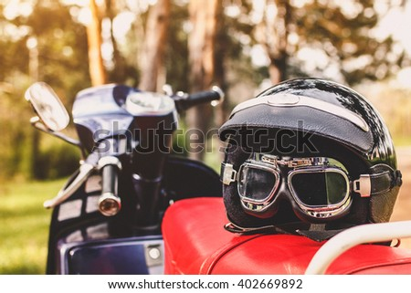 Retro motorcycle helmet with glasses on old scooter - stock photo