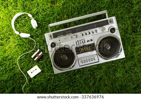 Retro music blaster and earphones over green grass, studio shot - stock photo