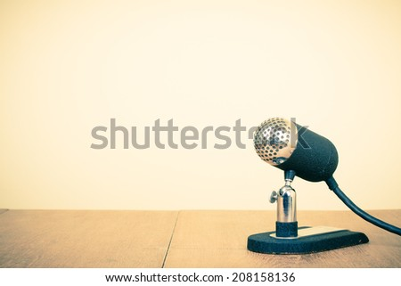 Retro old microphone on table. Vintage style filtered photo - stock photo