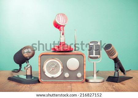 Retro old microphones and wooden radio front mint green background - stock photo