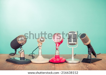 Retro old microphones for press conference or interview on table - stock photo