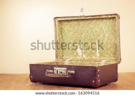 Retro old open travel suitcase on floor - stock photo