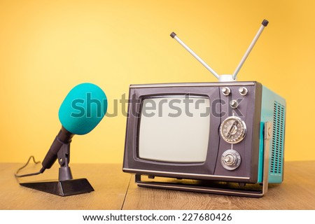 Retro old portable TV and microphone front gradient yellow background - stock photo