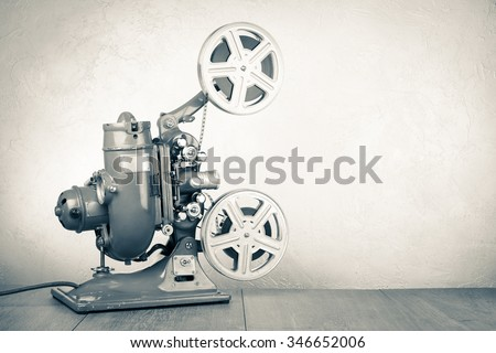 Retro old reel movie projector for cinema. Vintage style sepia photo - stock photo