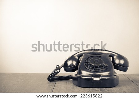 Retro old rotary telephone on table. Vintage style sepia photography - stock photo