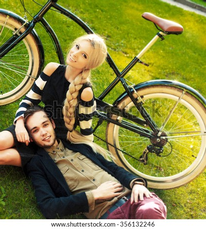 Retro old style photo with noise and scratches Young handsome hipster couple posing outdoor in the park having fun with vintage bicycle  - stock photo
