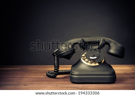 Retro old telephone on table front dark background - stock photo