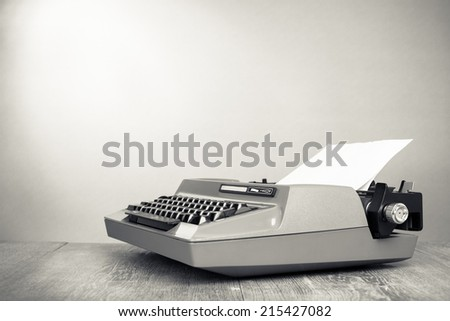 Retro old typewriter on oak wooden table. Vintage style sepia photo - stock photo