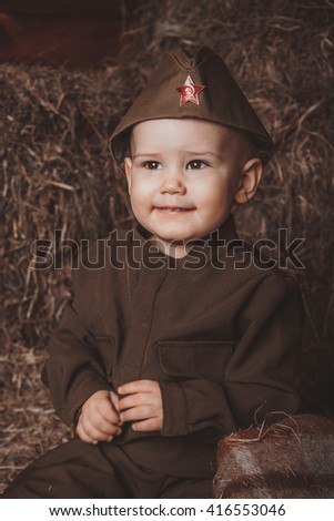 Retro! One year smiling baby dressed in Second World War russian uniform.  Hay background - stock photo
