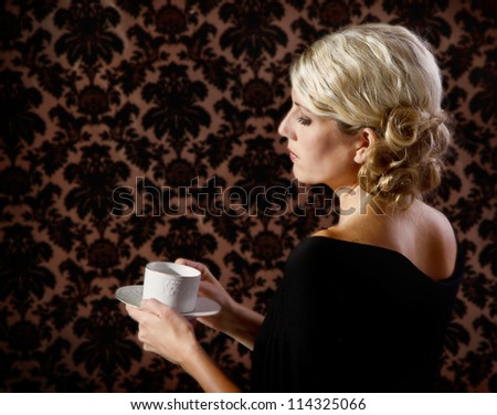 Retro or vintage looking woman drinking tea or coffee - stock photo