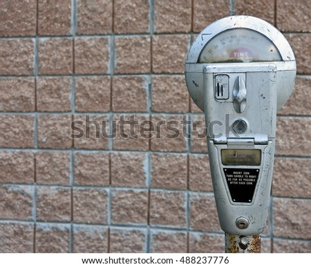 retro parking meter with brick wall background