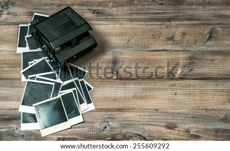 Retro photo camera and frames on rustic wooden background. Vintage style toned picture - stock photo