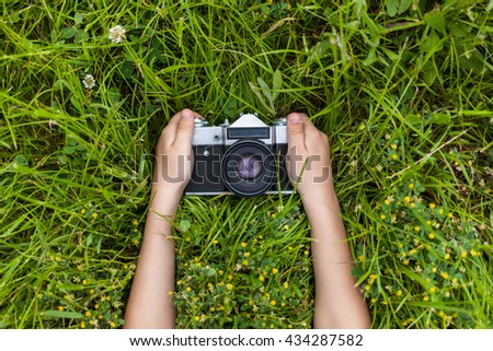 Retro photo camera in little boy hands. Green summer garden. Young photographer. - stock photo