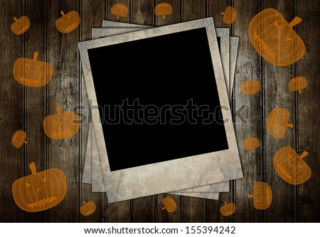 Retro photo frames on brown wooden background with pumpkins - stock photo