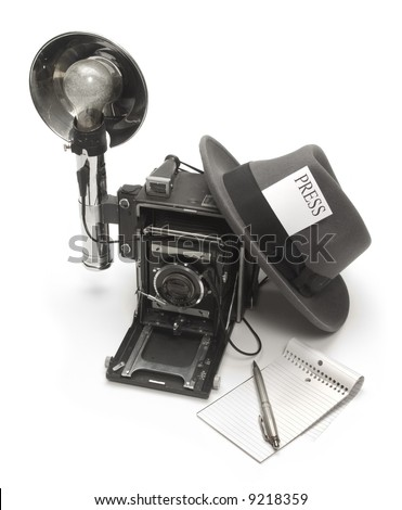 Retro photo journalist camera, fedora hat with a press pass in the headband, and ballpoint pen with notepad - stock photo