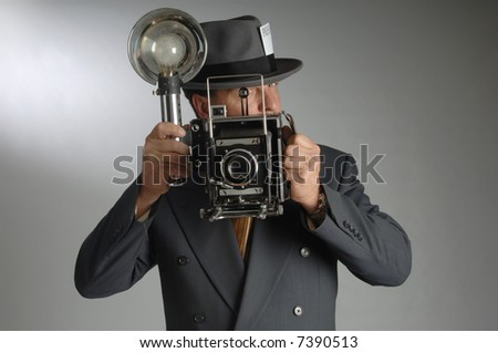 Retro photo journalist wearing a Fedora hat and holding a vintage camera with flash bulb - stock photo