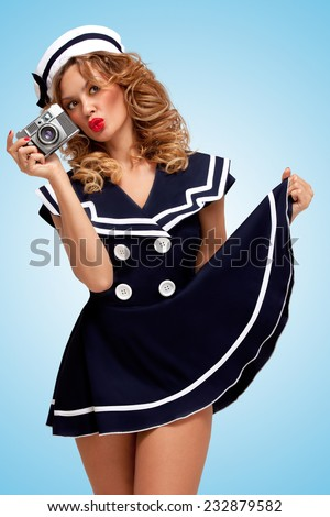 Retro photo of a glamorous pin-up sailor girl with an old vintage photo camera showing emotions on blue background. - stock photo