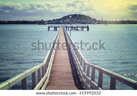 Retro photo of a long pier over blue sea water on a fine day. Soft focus. Grain - stock photo