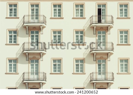 Retro Photo Of Apartment Complex Facade With Windows And Balconies - stock photo