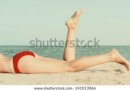 Retro Photo Of Girl Relaxing Her Feet On The Ocean Beach - stock photo