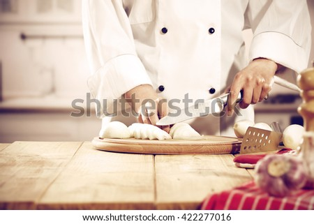 retro photo of kitchen interior and cook with knife  - stock photo