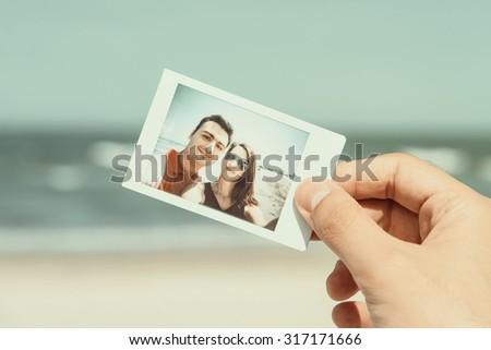 Retro Photo Of Man Hand Holding Instant Photo Of Happy Couple On Beach - stock photo