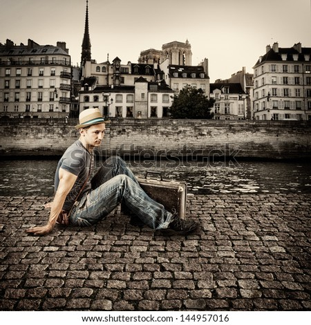 Retro photo of young handsome man traveler, sitting on the pavement promenade by the river in a European city - stock photo