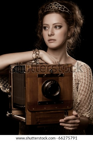 Retro photo of young woman standing near the outdated camera - stock photo