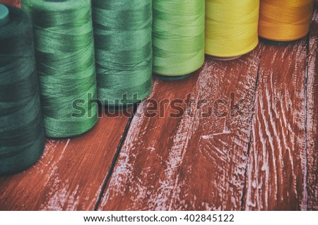 Retro photo thread spools for sewing and needlework on the background of the old red wooden table - stock photo