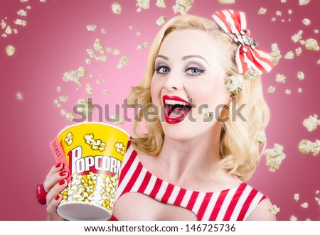 Retro photograph of a beautiful vintage girl with surprise expression watching premier film at movie theater amongst raining popcorn. Classic movies concept - stock photo