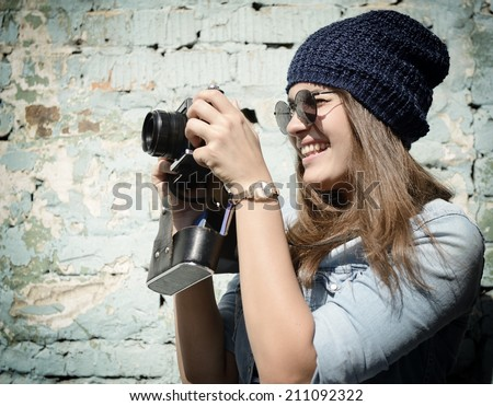 Retro photographer. Modern urban girl has fun with vintage photo camera outdoor near grunge wall, image toned. - stock photo