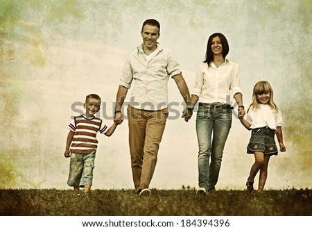 Retro photography of a family on green summer grass meadow having happy life - stock photo