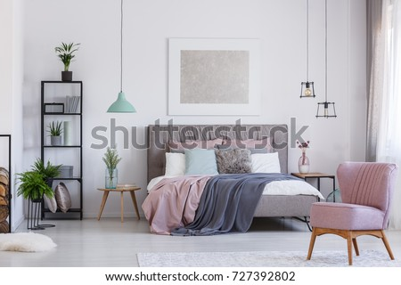 Retro pink chair in adorable pink bedroom with pastel bedding on bed and flowers in glass color vase on table